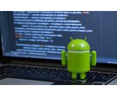 Android-Figur mit Code auf Comoputer-Bildschrim im Hintergrund