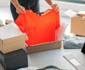 Frau packt T-Shirt aus Online-Lieferung aus