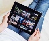 Person liegt mit iPad auf Couch und streamt Filme