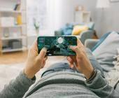 Mann spielt auf seinem Smartphone