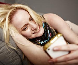 Frau liegt auf Sofa und vergnügt sich mit Handy