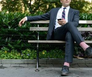 Mann sitzt mit Handy auf Bank