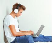 Junge hört Musik am Laptop